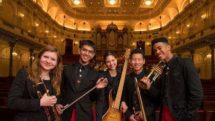 Five teenage musicians with black blazers and red pants stand in the Royal Concertgebouw.
