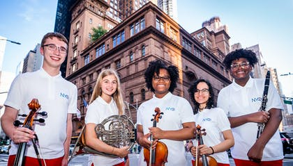 Five teenage musicians with white polos and red pants stand on the corner outside Carnegie Hall.