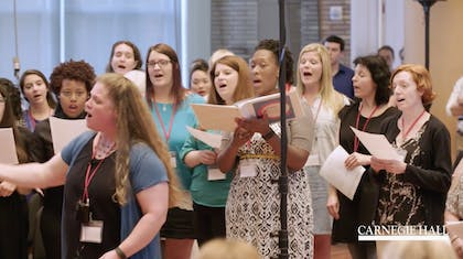 A presenter leads a choir of teachers