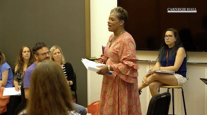 A woman speaks before a group of teachers in a workshop