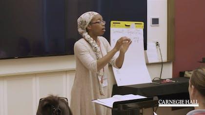 A teacher conducts a class of educators in a vocalization