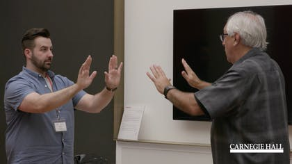 A presenter and a teacher hold up their hands toward each other