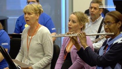 A group of teachers sing as a flutist plays