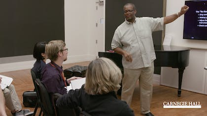 A man speaks before a group of teachers in a workshop