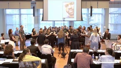A presenter conducts a choir of teachers as an audience of teachers watches