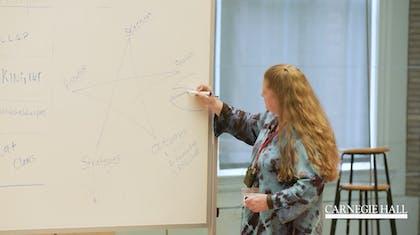 A presenter writes on a whiteboard