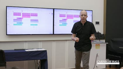 A presenter speaks as two monitors behind him display graphs