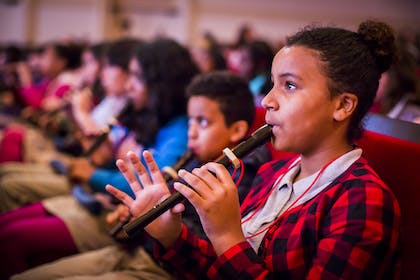 A young girl in a red flannel shirt plays the recorder with other kids playing in the background.