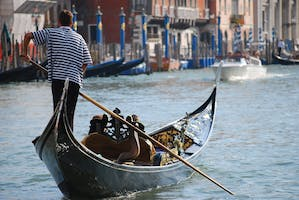 A gondolier rows his boat down the Venice canal
