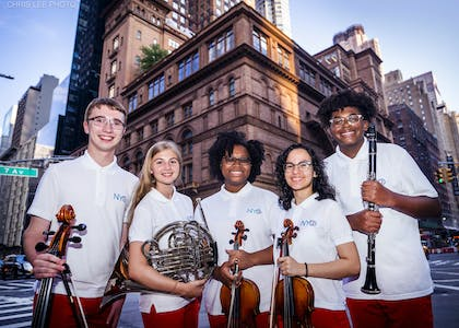 Five teenage musicians wearing white polos and red pants stand on the corner outside Carnegie Hall.