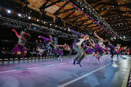 A group of dancers jump in mid-air with their arms behind them in a large performance center.