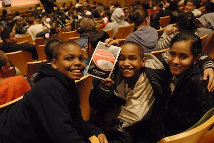 Three children seated in Zankel Hall hold up a Playbill for Perelman American Roots.