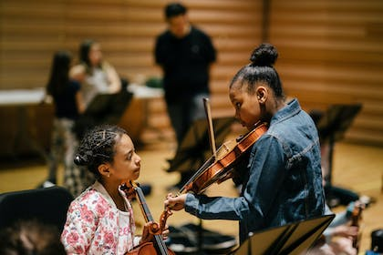 An older girl in a jean jacket shows a younger girl in a floral jacket her violin in a rehearsal.