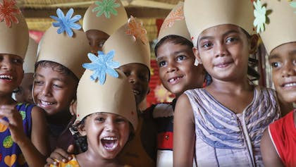 Laughing children wearing paper hats