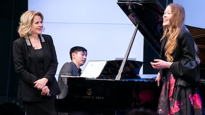 Accompanied by a pianist, a young woman sings as Renée Fleming observes.