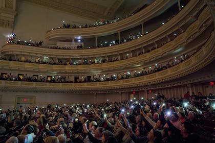 Audience members in Stern Auditorium / Perelman Stage hold up lights on their cell phones.