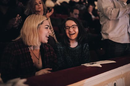 Two young women smile and laugh during a concert in Stern Auditorium / Perelman Stage.