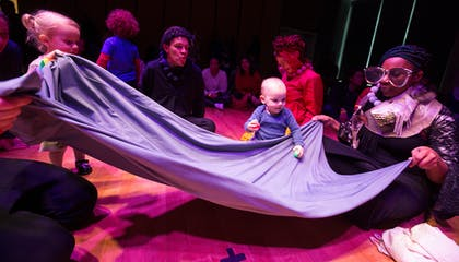 In a dark room, toddlers play with a parachute held by an actress with comically sized glasses.