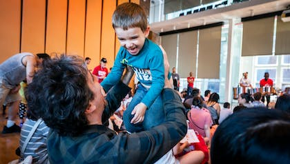 A man holds a happy young boy in the air during a performance in the Weill Music Room.