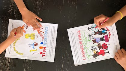 Two pairs of kids' hands color on activity pages.