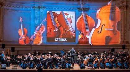 Images of cellos projected on the wall behind an orchestra