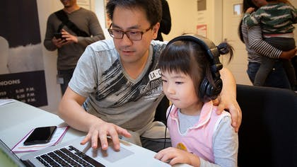 A man with glasses works on a laptop with a young girl wearing headphones and a pink shirt.