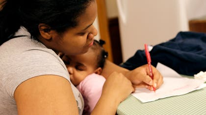 A mother holds her sleeping baby while writing lullaby lyrics