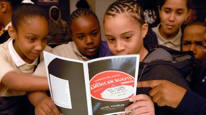 "Young students peruse the Carnegie Hall book ""American Roots"" together"