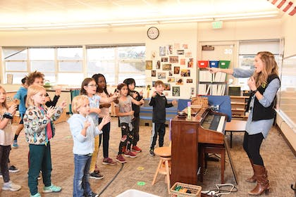 A young woman points at her elementary students from behind a brown piano in a bright classroom.