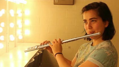 A young female musician plays the flute