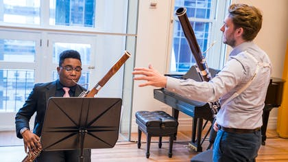 A teacher instructs a young musician