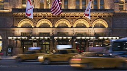 Taxi cabs drive by Carnegie Hall at night
