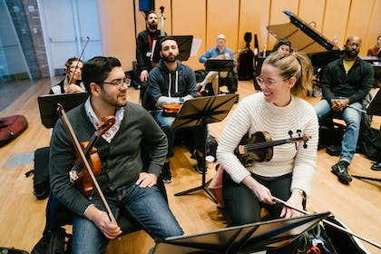Two violinists converse as other educators look on during Carnegie Hall's Music Educators Workshop.