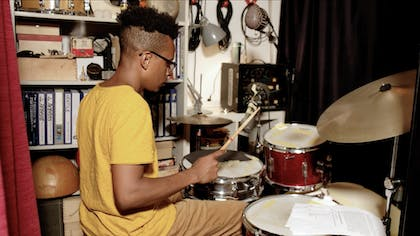 Charles Burchell plays the drums in his studio.