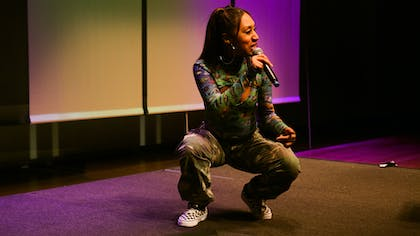 Queen Jo, a female MC in a patterned outfit, performs in the Black Thought master class showcase.