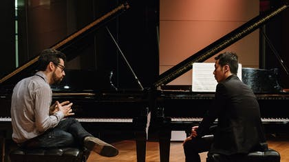 Pianist Jonathan Biss coaches Soohong Park; both men sit in front of pianos, facing each other.
