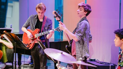 Three Future Music Ensemble members perform on stage with electric guitars and a drum set.