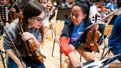 Two violinists from NYO-USA and RCO Young share a stand in a joint rehearsal.