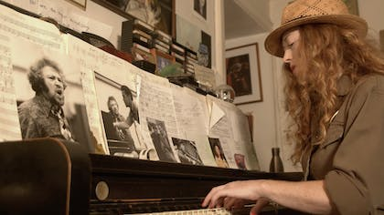 Bridget Barkan plays a piano covered in sheet music and photographs of musicians.