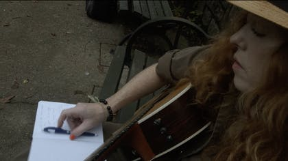 Bridget sits on a bench with her guitar and writes in her notebook.