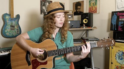 Bridget Barkan plays an acoustic guitar in her studio.