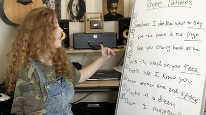 Bridget outlines rhyme patterns in her song on a whiteboard.