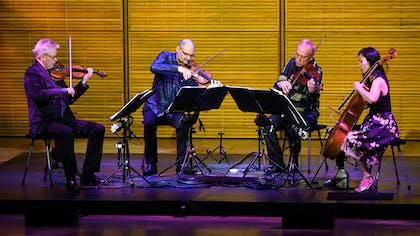 Kronos Quartet performs in Zankel Hall, bathed in contrasting purple and gold light.