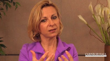 Screenshot of soprano Natalie Dessay discussing the art of recital on camera
