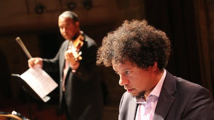 A man with curly hair stands in the foreground, an out-of-focus violin player stands behind him