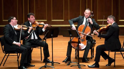 A string quartet comprising four men in black suits performing on a wooden stage