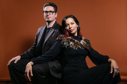 Francesco Turrisi and Rhiannon Giddens sit in front of a solid burnt sienna background.